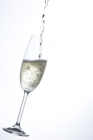 cava: Pouring champagne into a glass in white background