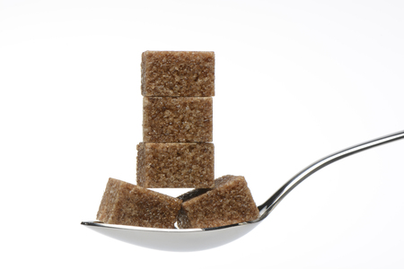 calory: Cubes of brown sugar on a spoon