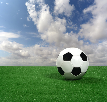 photomontage: Soccer ball, artificial grass and sky photomontage