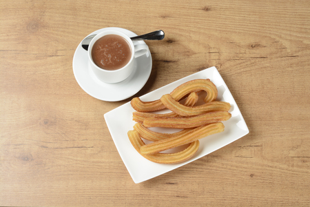 churros: Chocolate and churros on a plate on brown wooden background