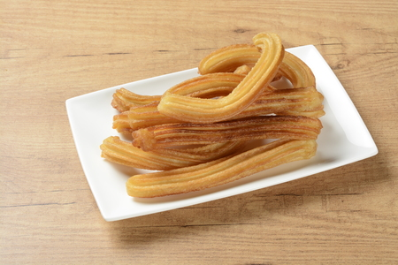 churros: Churros on a plate on brown wooden background Stock Photo