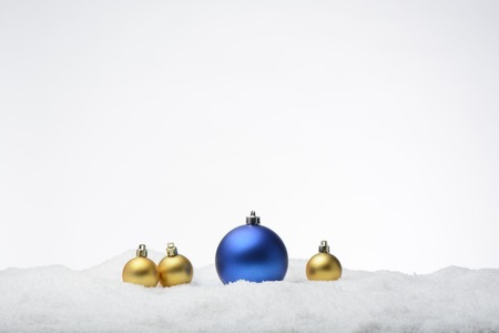 christmas ornamentation: Christmas balls on snow. Blue and golden Stock Photo