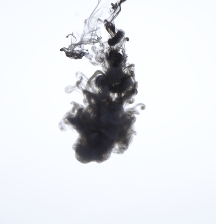 Black ink petering out in water, white background