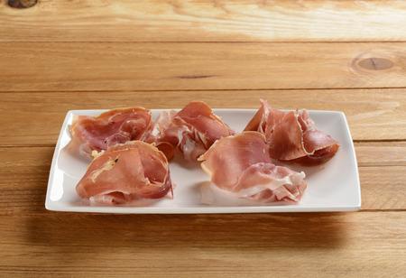 serrano: Serrano ham on a plate on wooden table