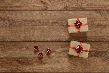christmas ornamentation: Gift boxes and red decorative Christmas balls on wooden background, composition as a card Stock Photo