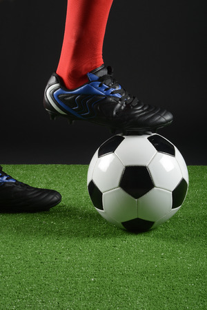 Football player with a foot over the ball