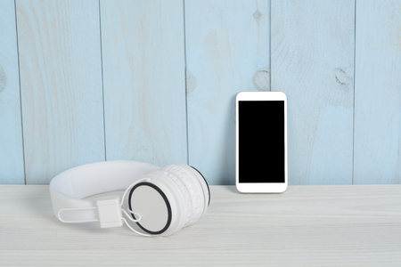 Auriculares y teléfono en mesa de madera blanca y pared azul