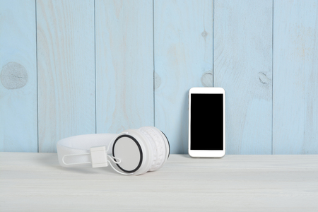 Headset and telephone on white wooden table and blue wall Foto de archivo