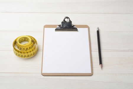 Notebook folder, pencil and measuring tape for tailor on white wood background Stock Photo