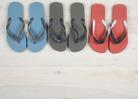 flip flops: Flipflops on a white wooden background, colors red, gray and blue Stock Photo