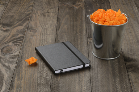 Bucket of brass filled with crumpled paper or orange posit and black pad, on wooden background