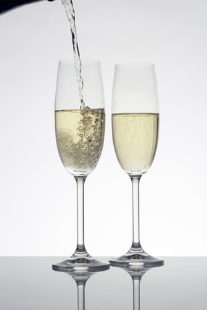 Pouring champagne in two glasses, white background Stock Photo