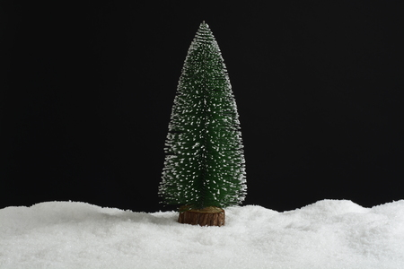 Small artificial Christmas tree in the snow, card