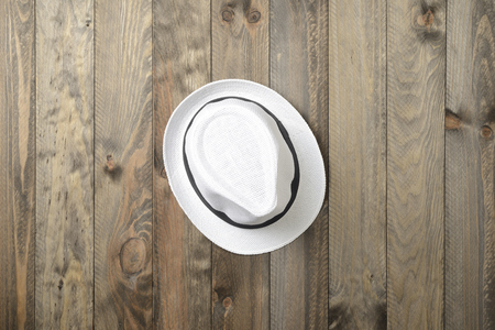 White hat on wooden background, seen from above Stock Photo