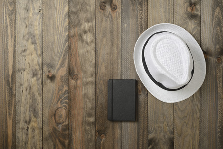 White hat and black notebook on wooden background, seen from above Stock Photo