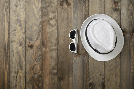 White hat and sunglasses on wooden background, viewed from above
