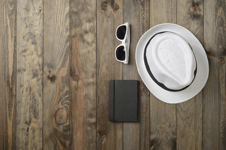 White hat, sunglasses and notebook on wooden background, viewed from above Stock Photo