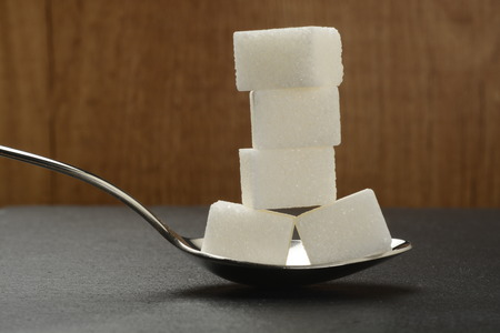 Lumps of sugar in a spoon on black background, or sugar cubes