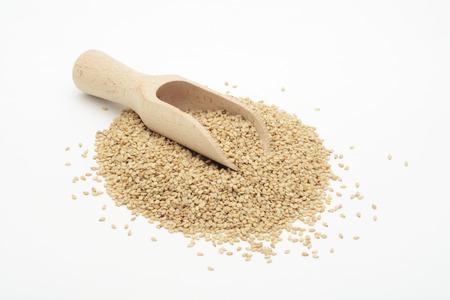 Natürlicher Sesam in einem Holzlöffel, rohe Samen