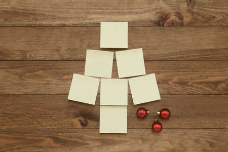 Notes or posit in the form of Christmas tree on brown wooden background