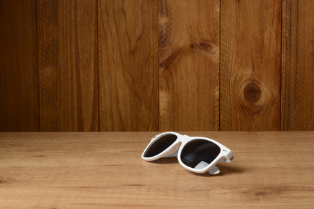 White sunglasses on brown wooden background