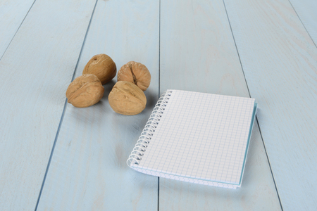 Walnuts and notepad on blue wooden background, blank notebook