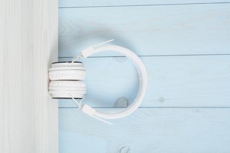 Cascos o auriculares en una mesa de madera blanca y pared azul