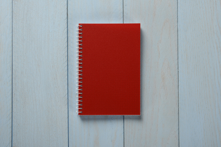 Red notebook on blue wooden background, concept