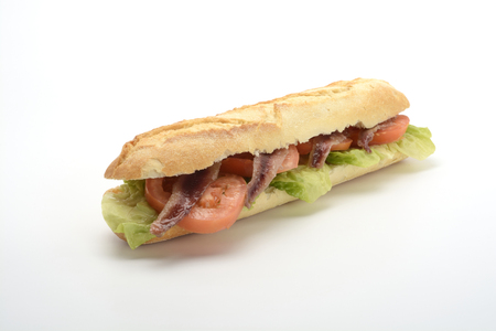 Anchovy sandwich with tomato and lettuce on white background