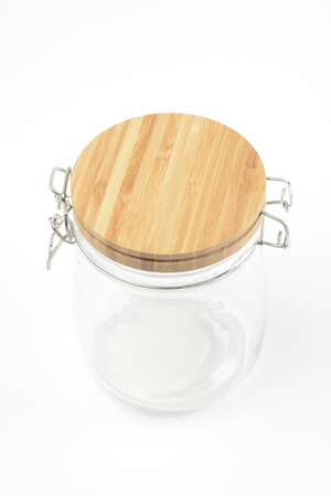 Glass jar with wooden lid on white background
