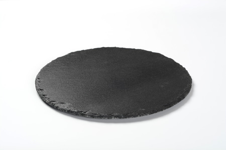 Round black slate plate on white background