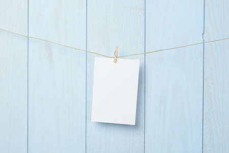 Card hanging on a rope over blue wooden Stock Photo