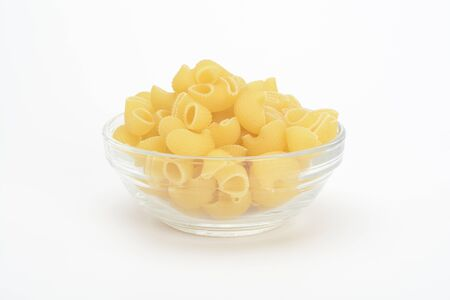 Raw pasta shaped elbow in a glass bowl
