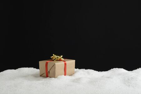 Gift box with red ribbon on the snow, black background