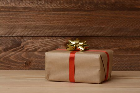Gift box on wooden brown background, red ribbon