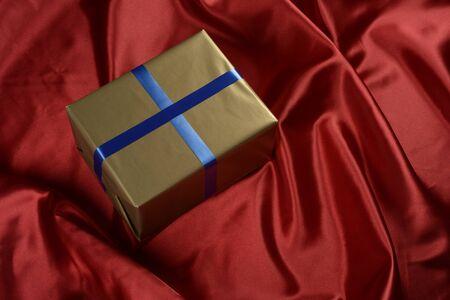 Caja de regalo de color dorado sobre fondo de tela de color rojo Imagens