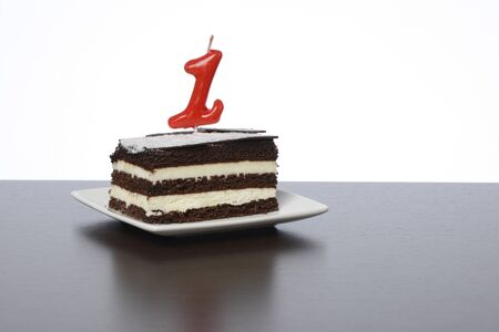 Cake with number one candle on brown background