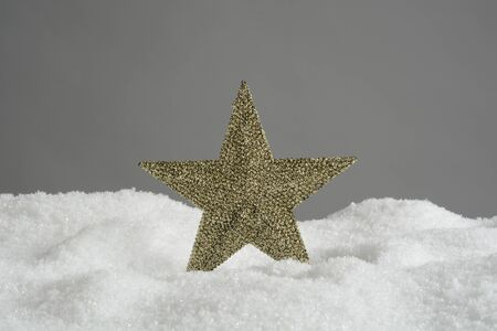 Golden star for decoration on Christmas in the snow
