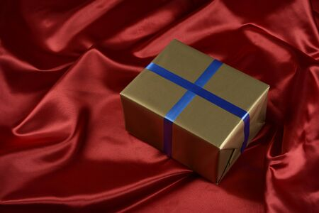 Gift box of golden color on a background of red cloth