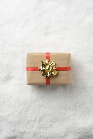Gift box in snow wrapped with red ribbon Stockfoto