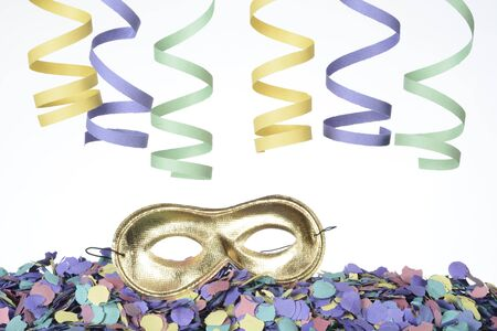 Detail of a carnival mask on confetti and ribbons on white background Stockfoto