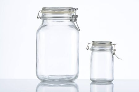 Two empty glass jar on white background