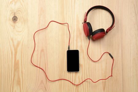 Phone and headphone on the wooden floor