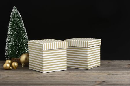 Golden and white striped gift boxes on wooden and black background 免版税图像