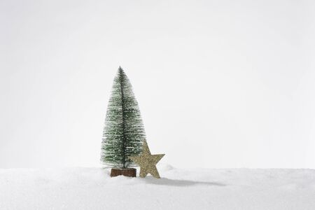 Decorative artificial christmas tree in artificial snow and one golden star, composition as a card or banner