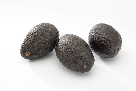 Three avocados on white background