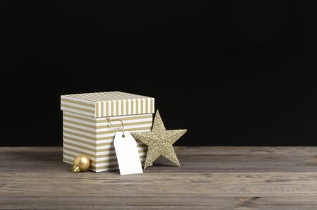 Golden and white striped gifts box on wooden and black background Фото со стока