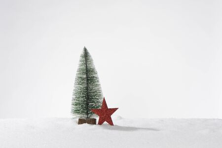 Decorative artificial christmas tree in artificial snow and one red star, composition as a card or banner