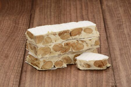 Hard nougat on wooden background, cut into pieces