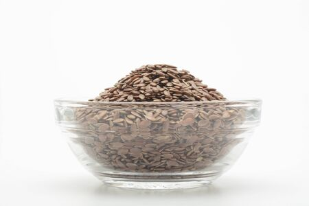 Brown flax seeds in a glass bowl on white background